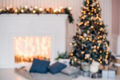 Julbakgrund med det upplysta granträdet och spis på huset arkivbild
