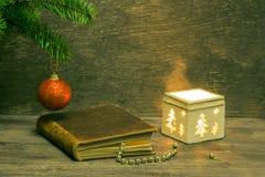 Julbakgrund med en gammal brun bok för röd boll och ett infall arkivfoto