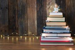 Julbakgrund med en hög av böcker, en ängel, stearinljus och royaltyfria foton