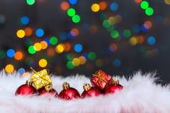 Julbakgrund med en röd prydnad, en guld- gåvaask och en fi Royaltyfri Fotografi