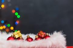 Julbakgrund med en röd prydnad, en guld- gåvaask och en fi Arkivfoto