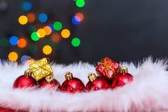 Julbakgrund med en röd prydnad, en guld- gåvaask och en fi Arkivfoton