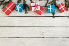 Julbakgrund med garneringar och gåvaaskar på träbräde arkivfoton