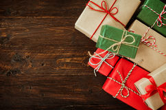 Julbakgrund med garneringar och handgjorda gåvaaskar på gammalt trä Royaltyfri Foto