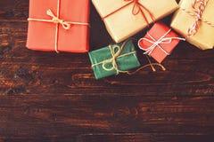 Julbakgrund med garneringar och handgjorda gåvaaskar på gammalt träbräde Fotografering för Bildbyråer