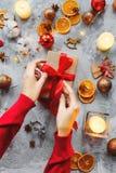Julbakgrund med garneringar och kvinnahänder, gåvan, stearinljus, apelsiner, kardemumma, klumpa ihop sig Begrepp av det närvarand royaltyfria bilder