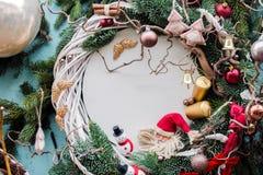 Julbakgrund med gran förgrena sig, struntsaker, stearinljus, snögubben, ängelvingar för bildfoto för kustlinje grön horisontalför Arkivfoto