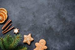 Julbakgrund med granträdfilialer, kanel och kakor Arkivfoto