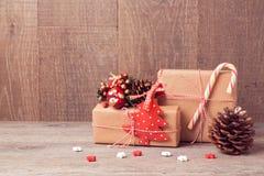 Julbakgrund med gåvaaskar och lantliga garneringar på trätabellen Royaltyfri Fotografi