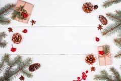 Julbakgrund med julgåvan, granfilialer, sörjer kottar, snöflingor, röda garneringar Xmas och lyckligt nytt år arkivfoton