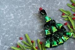 Julbakgrund med julgranen av choklader och candien arkivbild