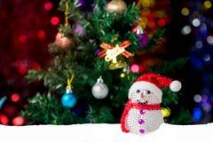 Julbakgrund med julgranen och snögubben på snö Arkivbilder