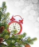 Julbakgrund med klocka- och snögranträdet Fotografering för Bildbyråer