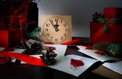 Julbakgrund med klockan, snögranträdet och gåvaaskar över trä märker inbjudningar Santa Claus Arkivfoto
