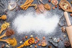 Julbakgrund med kryddor, muttrar, Rosines, ingefäran, kakaopulver, torkade apelsiner Arkivbilder