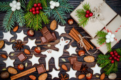 Julbakgrund med pepparkakakakor, gåvor, gran förgrena sig och kryddor på det gamla träbrädet Arkivfoto