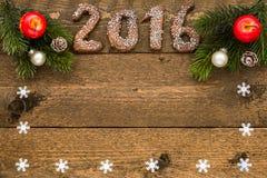 Julbakgrund med pepparkakan numrerar 2016, förgrena sig gran och garneringar med ramen för din text på det gamla träbrädet Arkivfoton