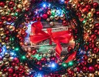Julbakgrund med röda och guld- struntsaker som omkring tänds, i mittgåvapengarna Top beskådar xmas för kortillustrationvektor arkivfoton