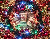 Julbakgrund med röda och guld- struntsaker som omkring tänds, i mittgåvapengarna Top beskådar Xmas-lyckönskan arkivfoton