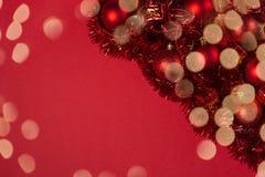 Julbakgrund med röda prydnader, den fluffiga girlanden och gnistrandebokehljus på röd kanfasbakgrund Greetin för glad jul arkivfoton