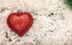 Julbakgrund med rött och grönt begrepp, den glänsande röda prydnaden kastar snöboll i hjärta som Shape på hörnet Royaltyfri Foto