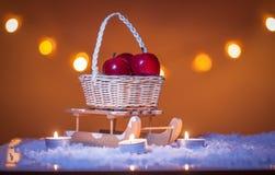 Julbakgrund med släden, korg med röda äpplen, stearinljus, snö, stjärnor och bokehljus arkivbilder