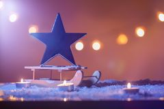 Julbakgrund med sleid, den stora stjärnan, stearinljus, snö och bokehljus Royaltyfri Fotografi