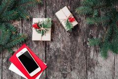 Julbakgrund med smartphonen, julgåva, granfilialer på träbakgrund med granfilialer arkivfoto