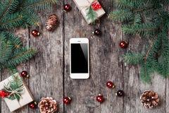 Julbakgrund med smartphonen, julgåva, granfilialer på träbakgrund med granfilialer royaltyfri foto