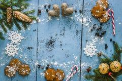Julbakgrund med snöflingan, pepparkakan, godisrottingen, hjärtor och garnering för granträd Royaltyfria Bilder