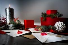 Julbakgrund med stearinljuset, granträdet och gåvaaskar över trä märker inbjudningar Santa Claus Arkivfoton