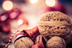 Julbakgrund med valnötter, röda klockor och stearinljus Royaltyfria Foton