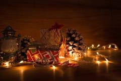 Julbakgrund på trä med en röd prydnad, en guld- gåvaask, bär och en gran i snö Royaltyfri Fotografi