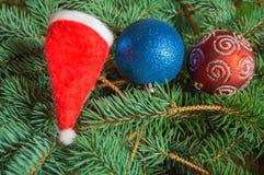 Julbakgrund, röd hatt Santa Claus, julbollar på prydliga filialer Arkivfoton