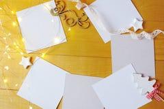 Julbakgrundskraft ark av papper med stället för din text och stjärnor och girland för vit jul på en guld Royaltyfria Bilder