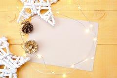 Julbakgrundskraft ark av papper med stället för din text och vita jul stjärna och girland på en träguld Arkivfoto