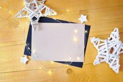 Julbakgrundskraft ark av papper med stället för din text och vita jul stjärna och girland på en träguld Royaltyfri Bild