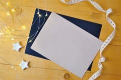 Julbakgrundskraft ark av papper med stället för din text och vita jul stjärna och girland på en träguld Arkivfoton