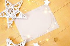 Julbakgrundskraft ark av papper med stället för din text och vita jul stjärna och girland på en träguld Arkivbilder