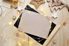Julbakgrundskraft ark av papper med stället för din text och vita jul stjärna och girland på trä Fotografering för Bildbyråer