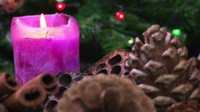 Julbakgrundsstearinljus och kottar arkivfilmer