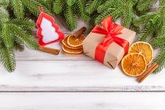 Julbaner med det gröna trädet, giftbox, handgjord filtgarnering, apelsinen och kanel på vit träbakgrund Arkivbild