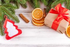 Julbaner med det gröna trädet, giftbox, handgjord filtgarnering, apelsinen och kanel på vit träbakgrund Arkivfoton