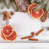 Julbaner med det gröna trädet, kottar, apelsinen, kanel och anteckningsboken på vit träbakgrund Royaltyfri Foto