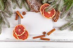 Julbaner med det gröna trädet, kottar, apelsinen, kanel och anteckningsboken på vit träbakgrund Royaltyfri Bild