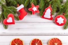 Julbaner med det gröna trädet, kottar, handgjorda filtgarneringar, apelsinen och kanel på vit träbakgrund Fotografering för Bildbyråer