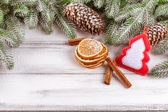 Julbaner med det gröna trädet, kottar, handgjorda filtgarneringar, apelsinen och kanel på vit träbakgrund Royaltyfri Fotografi