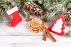 Julbaner med det gröna trädet, kottar, handgjorda filtgarneringar, apelsinen och kanel på vit träbakgrund Arkivfoto