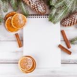 Julbaner med det gröna trädet, kottar, handgjorda filtgarneringar, apelsinen och kanel på vit träbakgrund Töm utrymme fo Arkivfoto