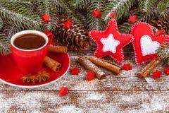 Julbaner med det gröna trädet, kottar, röd kopp med varm choklad, filtgarneringar, kanel på träbakgrund Fotografering för Bildbyråer